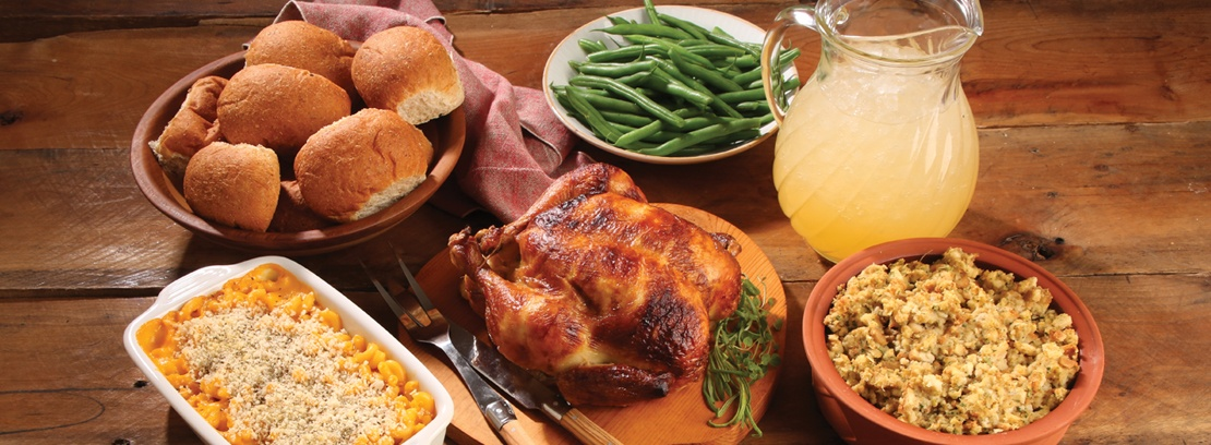 Roticerry chicken, green beans, corn, rolls and stuffing on wood table.