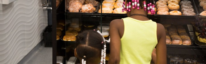 Photo of children selecting donuts from pastery case.